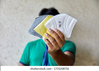 Adult Male holds three different types of Respirators (half face) in front of his face (Gray Grey Mask, White Mask, Yellow Mask)