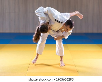 Adult male judoka throwing young female judo girl with hip throw
