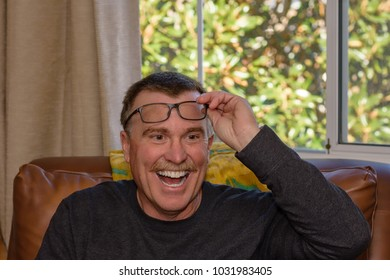 Adult male lifts glasses to happily share his reading