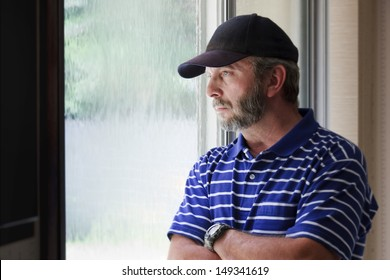 Adult male looking out a rain covered window might illustrate a recent job loss, unemployment, a troubled relationship, financial or health concerns or loss of a loved one.