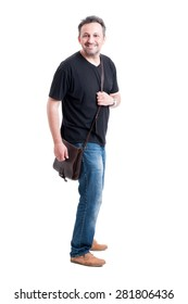 Adult male model wearing jeans, black t-shirt and bag on white background
