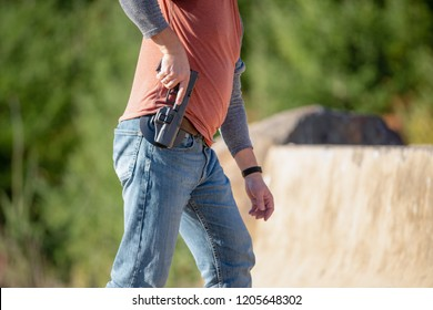 Adult male person in jeans and hoodie removing black handgun from a gun holster. Outdoor target range in Oregon.