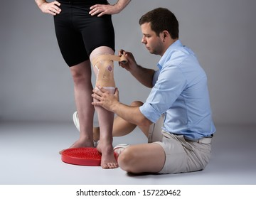 Adult male physiotherapist strapping the knee of a male patient.