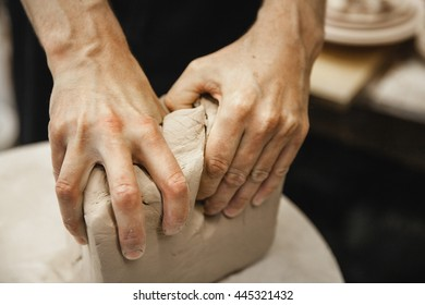 Adult male potter master preparing the clay on table. Front view, closeup, hands only, unrecognizable. Art and business, hobby and freelance working concept.