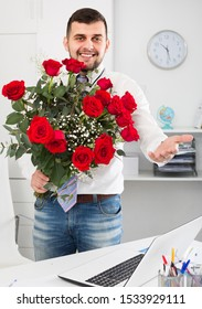 Adult male is presenting flowers and gift during romantic date.