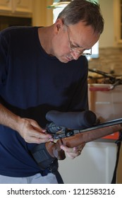 Adult male responsibly cleans his firearms indoors.