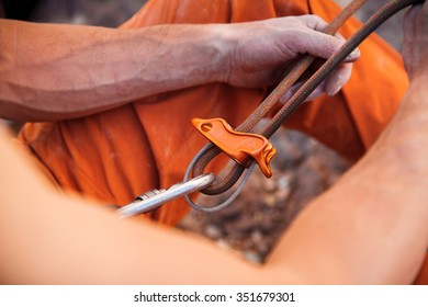 Adult male rock climber holding belay rope - hands closeup