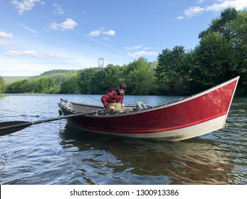 Adult male rowing a drift boat on the McKenzie River near Springfield Oregon.