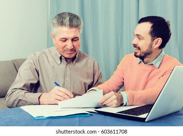 Adult male and sales manager discuss conditions of contract at home