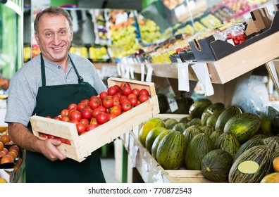 Adult male seller is demonstraiting fresh red tomatos in the store