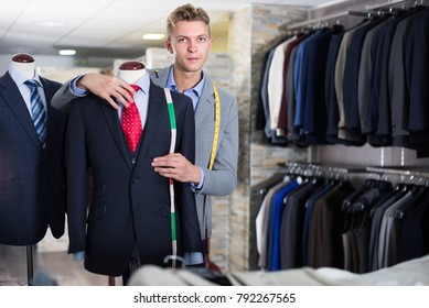 Adult male in shirt measuring business clothes jacket in the store