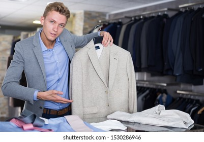 Adult male in shirt selling business clothes jacket in the store