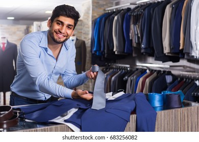 Adult male is showing jacket and tie that he chose in shop.
