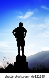 Adult male silhouette of a hiker contemplating peaceful sightseeing of mountains after a long trail.