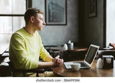 Adult male sitting in a empty cafe in front of a laptop and thoughtfully looking out the window