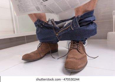 Adult male wearing jeans and shoes reading newspaper while sitting on the toilet seat in  the modern tiled bathroom at home