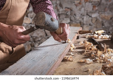 Adult male woodworker wearing plaid shirt and overalls using chisel and mallet to smooth down wood beam