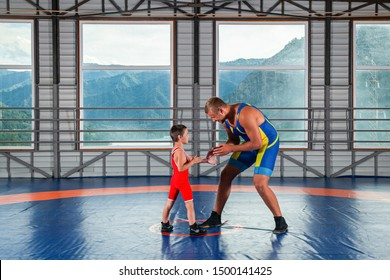 An adult male wrestler coach teaches the basics of wrestling and sets up a little boy to compete. The concept of child power and martial arts training. Teaching children Greco-Roman wrestling