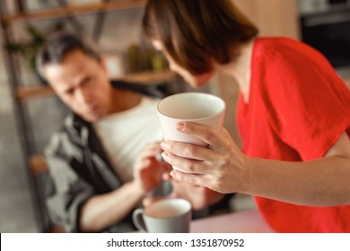 Adult man asking. Resolute mindless dark-haired woman carrying heavy ceramic cup and attacking her helpless husband