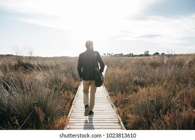Adult man with bag walking on wooden pier in tall grass and enjoying freedom in sunlight.