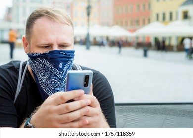 adult man in bandana as a face mask uses smartphone in city cafe terrace. solo outdoor activities. safety city walk