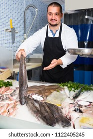 adult man in black apron and white cover-slut behind counter holding fish