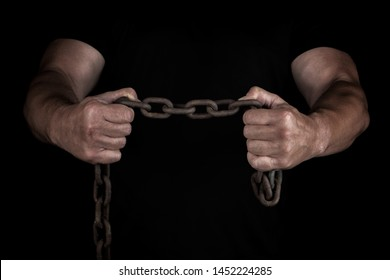 adult man in black clothes stands upright with strained muscles and holds a rusty metal chain, a concept of strength and endurance