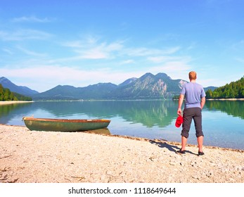 Adult man in blue shirt at old fishing paddle boat at mountains lake coast. Sunny spring day.