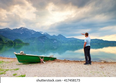 Adult man in blue shirt walk at old fishing paddle boat at mountains lake coast. Vintage photo effect