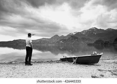 Adult man in blue shirt walk at old fishing paddle boat at mountains lake coast. Black and white photo