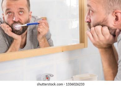 Adult man brushing his teeth looking at his bathroom mirror during morning hygiene routine being bored, hungovered or sleepy tired.