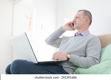 Adult man calling by smartphone at home