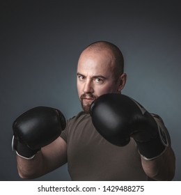 adult man with casual clothes and boxing gloves, looks directly at the camera. Concept of sport and determination in life.