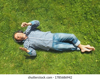 Adult man in casual clothes on the grass in the park. Listening music . Top view
