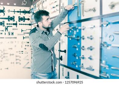 Adult man choosing new door handle in houseware store