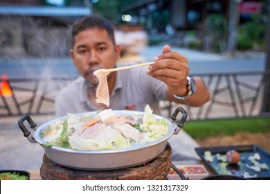 An adult man clamps Thai barbecue pork (Moo-Ka-Ta)  - famous Thai local food with need to do own cooking - food photography concept