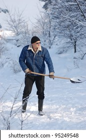Adult man clean owns road to home against snow.Near Kiev,Ukraine