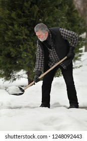 Adult man cleaning snow from sidewalk using shovel, winter time