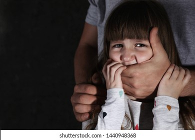 Adult man covering scared little girl's mouth on dark background, space for text. Child in danger