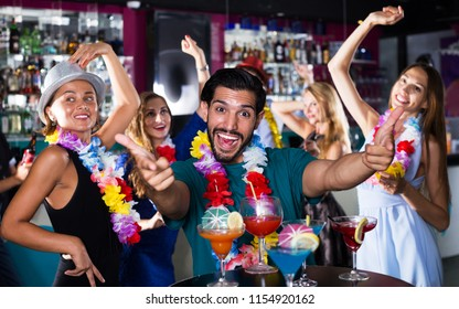 Adult man is dancing and having fun on the hawaiian party in bar