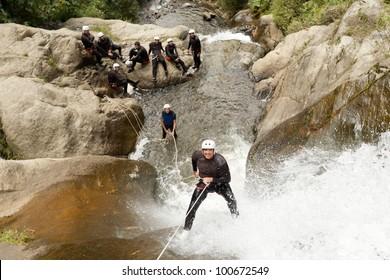 ADULT MAN DESCENDING AN ECUADORIAN WATERFALL IN A CORRECT POSITION