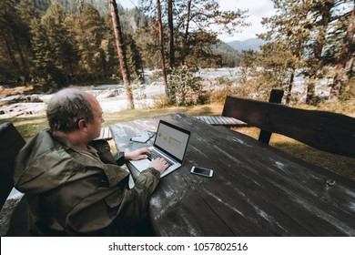 Adult man entrepreneur is sitting outdoors at the table of a mountain tourist resort during his vacations and working remotely via wi-fi with his business project using the laptop and gadgets around