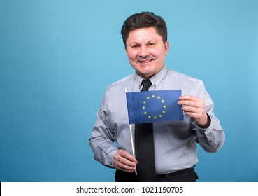 Adult man with the flag of the European Union standing on a blue background.