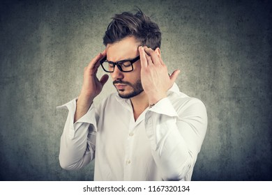 Adult man in glasses holding fingers on temples trying to concentrate on decision making