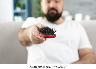 Adult man with hair brush at home, closeup