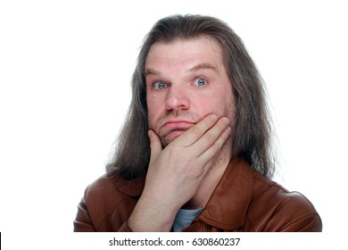 Adult man with hand to mouth and long hair looking thoughtfully at the camera, white isolated.