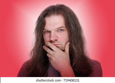 Adult man with hand to mouth and long hair looking thoughtfully at the camera. Red gradient background.
