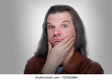 Adult man with hand to mouth and long hair looking thoughtfully at the camera, gray background.