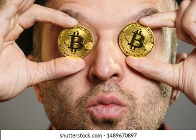 Adult man having bitcoin coin as pince nez in eye. Crypto internet currency banking concept.