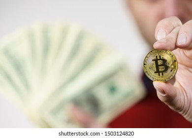 Adult man having bitcoin coin in hand comparing it into regular dolar cash. Crypto internet currency banking concept.